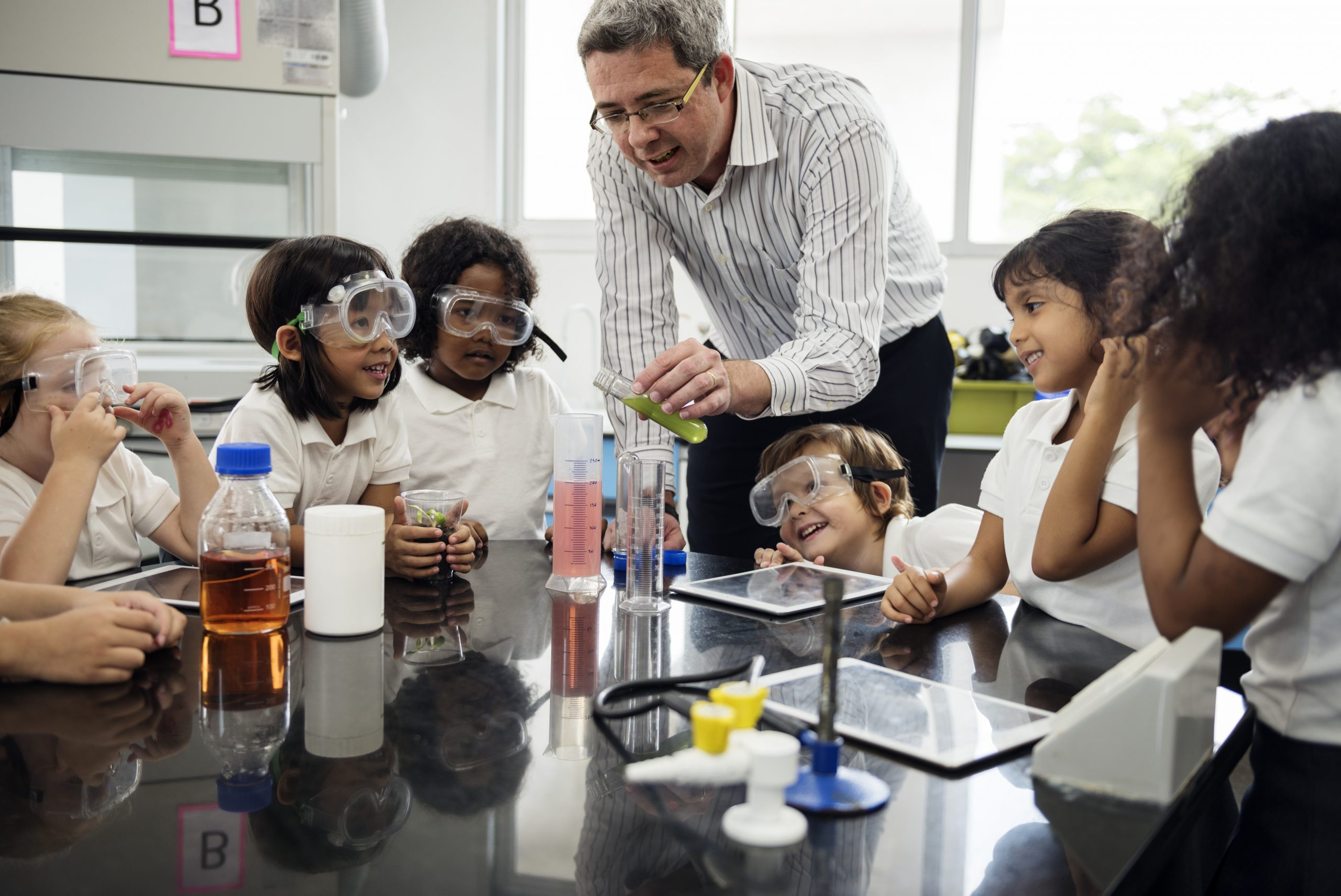 happy children in goggles look at teacher with test tube in science class
